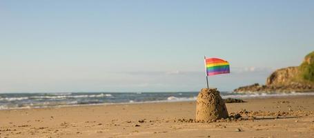 Regenboogvlag op een zandkasteel - zee in de verte foto