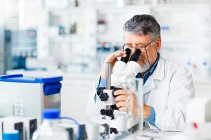 senior mannelijke onderzoeker uitvoeren van wetenschappelijk onderzoek in een lab foto