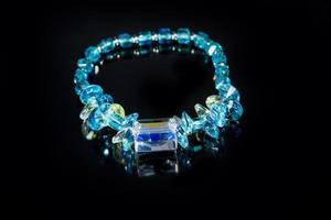 mooie blauwe plastic armband op zwarte achtergrond foto
