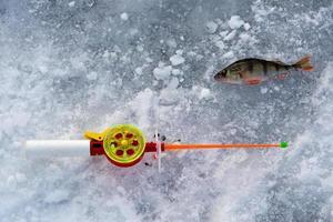 de hengel voor wintervissen ligt bij een gat foto