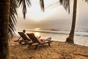 koppel op de ligbedden op het tropische strand foto