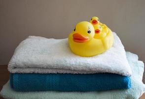 gele badeendjes op een stapel gevouwen handdoeken foto