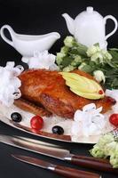 geroosterde eend gevuld met appel, gegarneerde kerstomaatjes en olijven foto