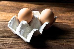 eieren in kartonnen doos op houten achtergrond