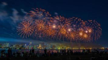 menigte kijken naar vuurwerk boven de rivier foto