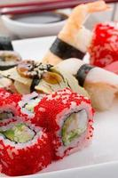 sushi ingesteld op een witte plaat op vintage houten achtergrond foto
