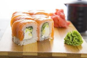 sushi op een houten plaat gete die op witte achtergrond wordt geïsoleerd foto