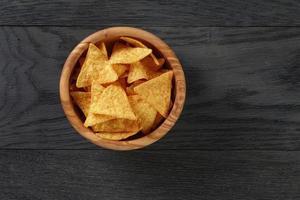 tortillachips in olijf houten kom op houten tafel foto