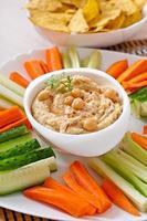 gezonde zelfgemaakte hummus met groenten, olijfolie en pitabroodjes foto