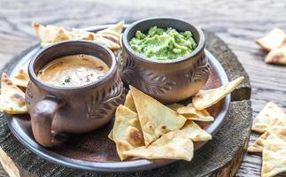kommen guacamole en queso met tortillachips foto