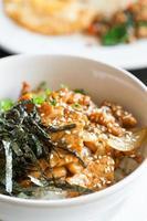 gebakken varkensvlees en rijst met zeewier bovenop foto