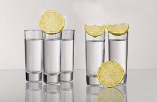 drie gouden tequilaschoten met kalk die op witte achtergrond wordt geïsoleerd