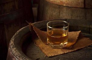 glas cognac in de kelder met oude vaten gestapeld foto
