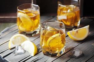koude whisky met ijs en citroen op de vintage tafel foto