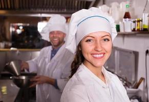 chef-kok en zijn helper in bistro keuken foto
