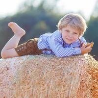 grappige kleine jongen jongen liggend op stapel hooi en glimlachen foto
