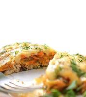 gebakken vis met kaassaus, wortelen en uien.