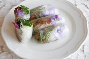 huisgemaakte rijstpapierrollen met eetbare bloemen foto