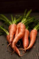 rauwe wortelen op houten tafel foto