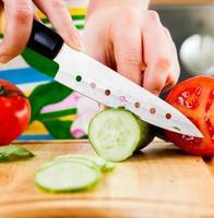 vrouw handen snijden komkommer foto
