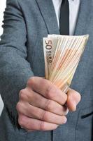 man in pak met een prop van eurobiljetten foto