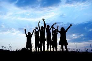 silhouet, groep gelukkige kinderen spelen op weide, zonsondergang, s