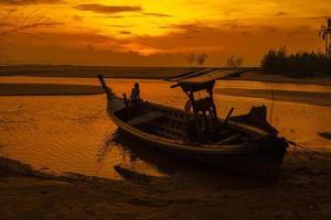 lokale boot op het strand bij zonsondergang foto