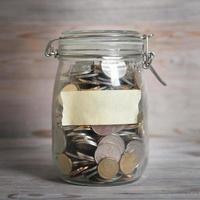munten in glazen geld pot met blanco label foto