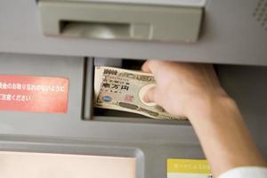 geld in de geldautomaat steken foto