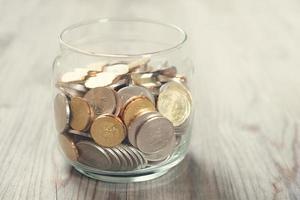 munten in glazen geld pot foto