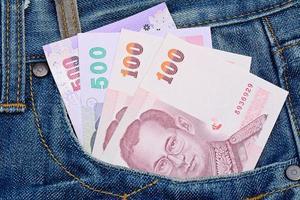 Thaise bankbiljetten in jeanszak voor geld en bedrijfsconcept foto