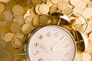 mooie oude klok die op één gouden muntstukkenachtergrond blijft. tijd foto