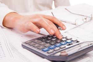 handen van zakenman met rekenmachine foto