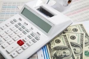 rekenmachine en diagrammen en geld op een zakelijke achtergrond foto
