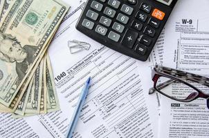 belasting vormt 1040 met de bril, geld en de pen foto
