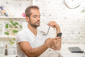 jonge executive op zoek naar zijn mobiel foto