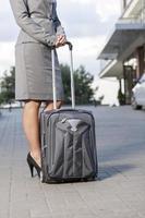 laag deel van zakenvrouw permanent met bagage op oprit foto
