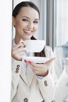 portret van gelukkige zakenvrouw met koffie in kantoor foto