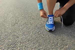 jonge vrouw loper koppelverkoop schoenveters op weg van de stad foto
