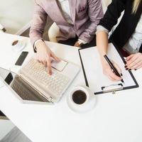 overhead van twee mensen die werken met laptop en klembord foto