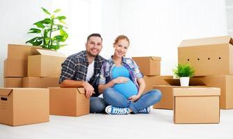 verhuizen naar nieuw appartement. familie zwangere vrouw en man met foto