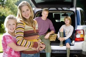 meisje omhelst moeder, vader en zoon (9-11) op de achtergrond, poort