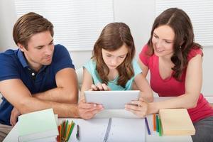 ouders bijstaan dochter in het gebruik van digitale tablet foto