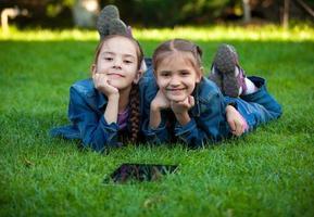 portret van twee kleine meisjes liggen op gras met tablet