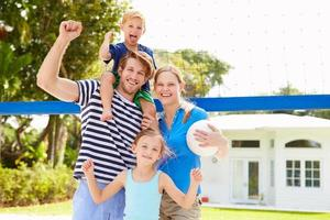 familie spelen van volleybal in de tuin foto