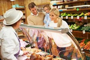 vrouwelijke verkoopmedewerker die familie in delicatessen dient foto