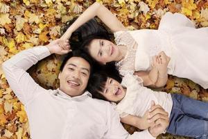 familie liggend op herfstbladeren foto