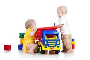 twee kleine kinderen spelen met kleur speelgoed