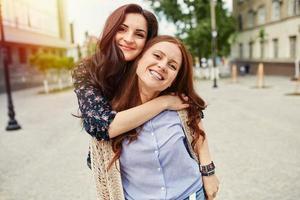 twee vrolijke zussen knuffelen foto
