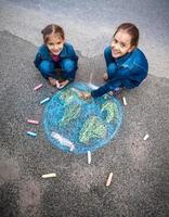 lachende meisjes tekenen van aarde met krijt op straat